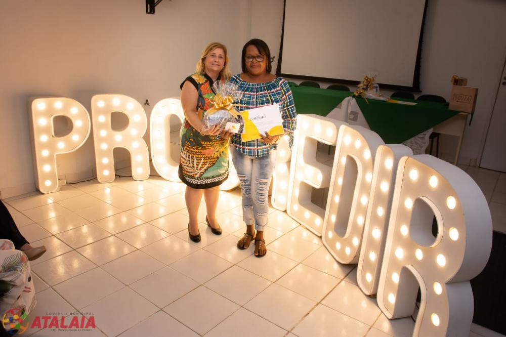 Primeira-Dama Rosiane Vigária entrega certificado a aluna concluinte.